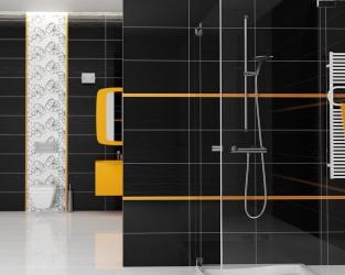 Błyszcząca czerń i pomarańcz oraz dekoracje kwiatowe podkreślają nowoczesność i styl łazienki